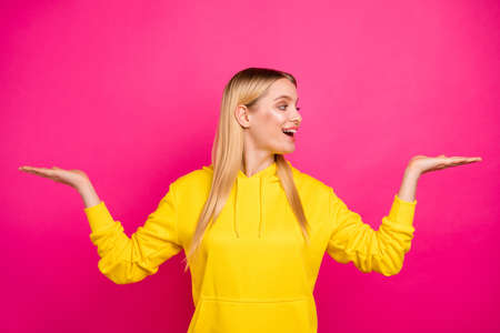 Funny excited lady presenting new products wear yellow hoodie pullover isolated pink background