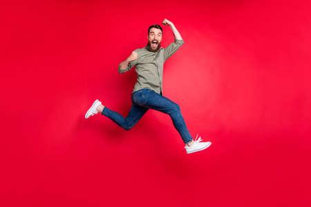 Foto de cuerpo entero de un hombre blanco guapo deportivo fuerte barbudo con camiseta gris corriendo en algún lugar con la victoria mientras está aislado con fondo rojo