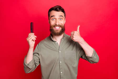 Photo of man advertising hairbrush showing that he liked using this thing while isolated with red background