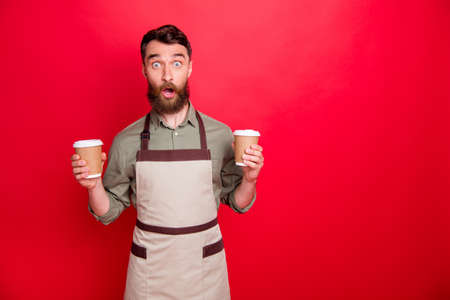 Portrait of his he nice attractive confused stunned wondered bearded guy waiter holding in hands cappuccino espresso latte choose choice isolated over bright vivid shine red background Reklamní fotografie
