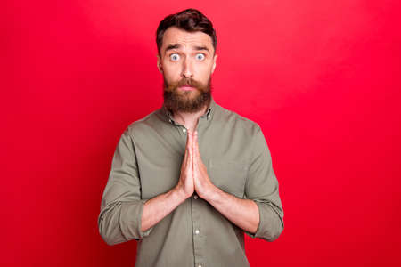 Photo of praying hoping man seeing something disappointing while isolated with red background