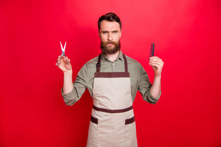 Portrait of his he nice attractive gloomy moody harsh bearded guy salon owner choosing deciding holding in hands instruments isolated over bright vivid shine red background