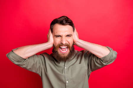Photo of upset man screaming with ears covered irritated and bothered while isolated with red background