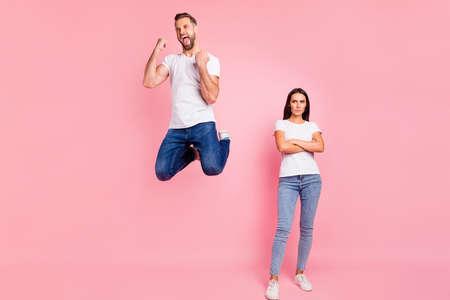 Ganzkörperfoto in voller Länge von einem lässigen Paar mit zwei Personen, das weiße T-Shirts Jeans Denim trägt, mit einem überglücklichen Mann und einer Frau mit verschränkten Armen, die sich beleidigt fühlt, isoliert mit pastellfarbenem Hintergrund