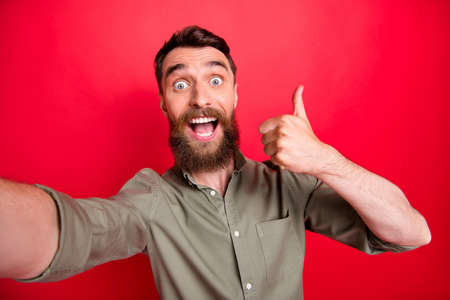 Photo of handsome overjoyed ecstatic man wearing grey shirt self shooting when thumbing up to you while isolated with red background
