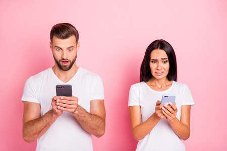 Portrait of his he her she two nice-looking attractive lovely charming confused discontent spouses using modern technology device gadget isolated over pink pastel background
