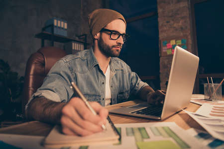 Photo of attentive guy work at dark time making notes of online lesson wear casual outfit sit modern office