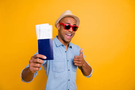 Portrait of cheerful man have ads recommend voyage wear trendy stylish denim jeans shirt cap eyewear eyeglasses isolated over yellow background Stock Photo