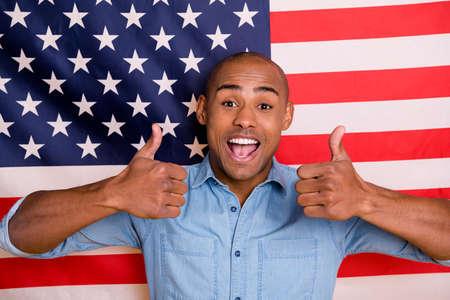 Il ritratto di gioventù funky divertente pubblicizza la grande buona immigrazione nazionale di vacanza divertirsi indossando la camicia di jeans del denim isolata sopra la bandiera di noi