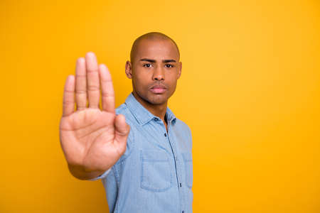 Portrait of strict person youth block hand isolated over yellow background Banco de Imagens