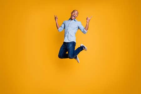 Portrait of childish playful youth have free time holiday scream fool isolated over yellow background Reklamní fotografie