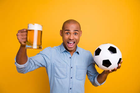 Photo of dark skin amazed guy hold hands ball beer glass support team yelling loud wear jeans denim shirt isolated bright yellow background