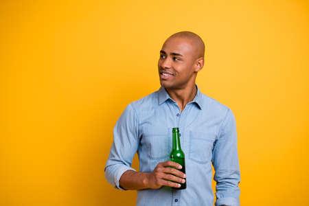 Photo de peau foncée macho soulever tenir la main bouteille de bière écouter amis sport bar porter jeans chemise en jean isolé fond jaune vif Banque d'images