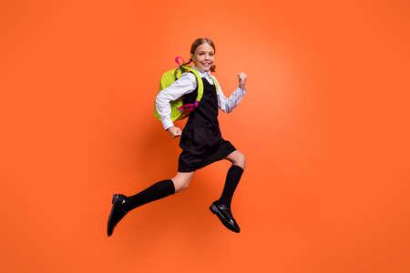 Ganzkörperansicht der schönen, attraktiven, fröhlichen, fröhlichen, fleißigen Pre-Teen-Mädchen-Nerd, die schnell in die erste Klasse zurück zur Schule läuft, einzeln auf hell leuchtendem orangefarbenem Hintergrund