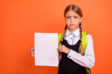 Portrait of her she nice attractive lovely disappointed unlucky pre-teen blonde girl showing bad fiasco mark score first grade isolated on bright vivid shine orange background