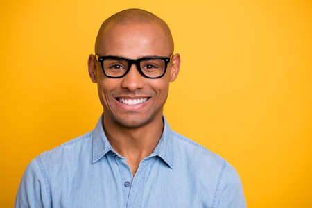 Photo of dark skin macho attractive appearance not smiling conference wear specs jeans denim shirt isolated bright yellow background