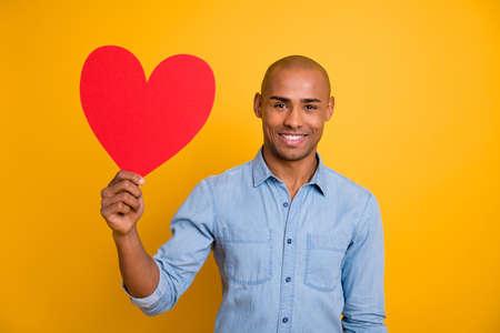 Photo of dark skin guy hold hand big paper postcard romance date invitation girlfriend wear jeans denim shirt isolated bright yellow background