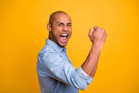 Profile photo of dark skin guy raise hands yell loud success achieve startup wear jeans denim shirt isolated bright yellow background