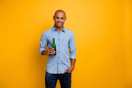 Closeup photo of dark skin macho raise hold hand beer bottle sport bar wear jeans denim shirt isolated bright yellow background Stock Photo