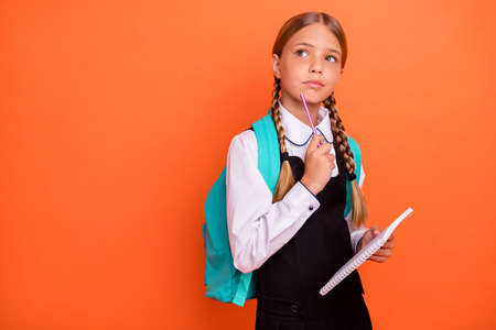 Portrait of her she nice attractive lovely charming cute minded nerd pre-teen girl learning academic subject isolated over bright vivid shine orange background