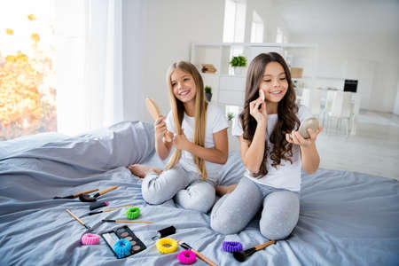 Portrait of attractive children people hold hand apply cosmetics feel leisure content dreamy sit white bed room indoors