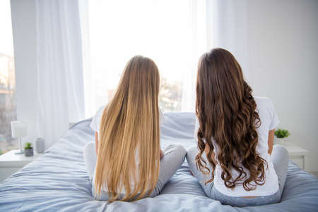 Foto vista laterale posteriore di affascinanti bambini amici anonimi sedersi camera da letto camera da letto al chiuso