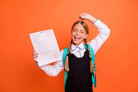 Portrait of nice attractive charming cute cheerful cheery successful glad pre-teen blonde girl demonstrating great grade rejoicing having fun isolated on bright vivid shine orange background