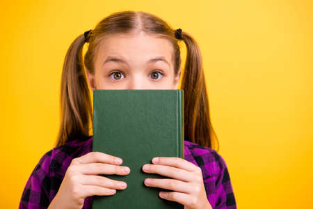 Close up photo of little lady pupil hold book hide half face pretty ponytails wear checkered shirt isolated yellow background Imagens