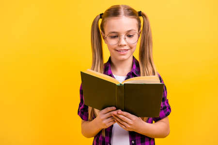 Closeup photo of small lady knowledge wondered reading story wear specs checkered shirt isolated bright yellow background Stock Photo