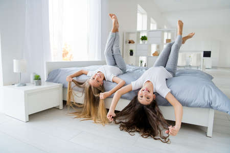 Ritratto di bambini carini che toccano il taglio di capelli lungo fanno facce divertite con la lingua fuori, si trovano in un'accogliente camera da letto bianca all'interno si sentono negligenti