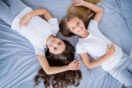 Top above photo of sweet children fellows look feel content have free time lie bed room indoors home house