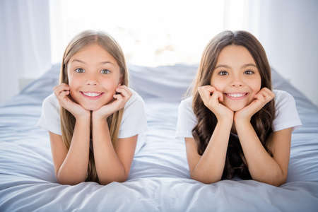 Close up photo of lovely charming kids hands chin touch lie bed room indoors brunette blonde hair