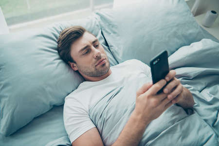 Top high angle photo of focused person holding modern technology reading information lying in bed room indoors