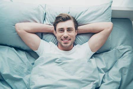 Foto de ángulo alto superior de la encantadora persona rubia acostada en la cama sonriendo con camiseta blanca en el interior de la habitación