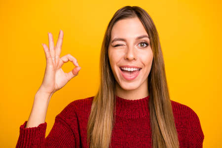 Photo of coquettish blinking pretty lady showing okey symbol wear pullover isolated yellow background