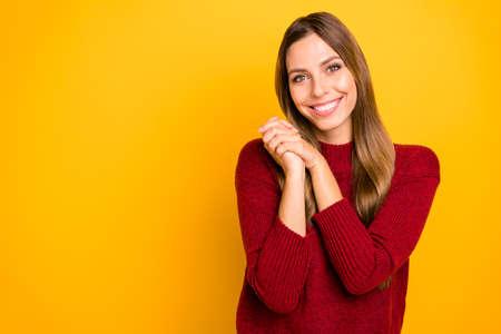 Foto der hübschen Dame, die überglücklich die Hände zusammenhält, tragen einen burgunderfarbenen Pullover isoliert auf hellgelbem Hintergrund