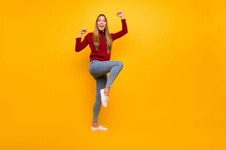 Full length photo of lady raising fists air cheerleading wear pullover isolated yellow background Stock fotó
