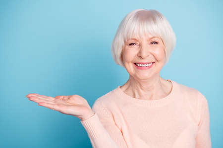 Portrait of charming person holding her palm smiling wearing pastel sweater isolated over blue background