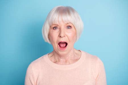 Portrait en gros plan d'une belle jolie jolie dame aux cheveux gris en bonne santé et bien soignée, expression de la bouche ouverte isolée sur fond bleu sarcelle bleu vert brillant vif Banque d'images