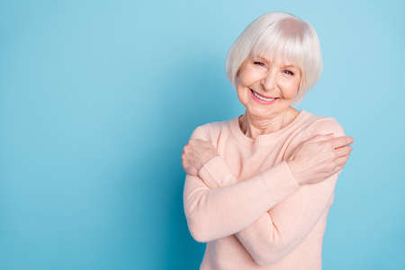 Portrait of cheerful nanny cuddling herself wearing pink pullover isolated over blue background