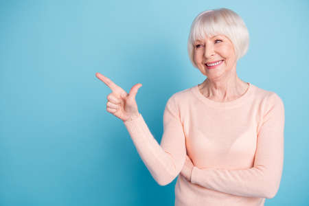 Portrait of pretty old woman pointing at copy space wearing pastel sweater isolated over blue background