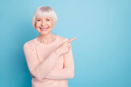 Portrait of lovely lady pointing at copy space having toothy smile isolated over blue background Banco de Imagens