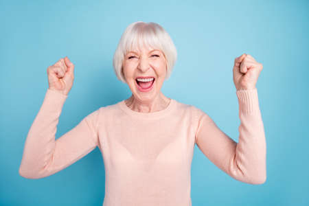 Portrait of delighted cheerful lady raising fists shouting yeah wearing pastel jumper isolated over blue background