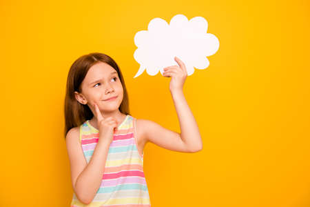 Portrait lovely kid holding paper card bubble touching chin wearing tank-top isolated over yellow background Stock Photo - 128473105