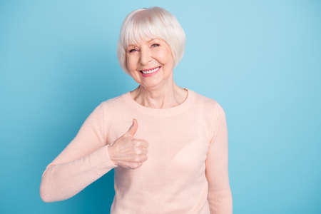 Portrait of cheerful lady looking, with toothy smile showing thumb up wearing pastel pullover isolated over blue background Banco de Imagens
