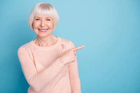 Portrait of pretty lady pointing at copy space smiling wearing pastel jumper isolated over blue background Banco de Imagens