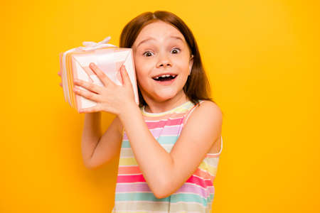 Portrait of lovely child holding present for 8-march screaming wow omg isolated over yellow background