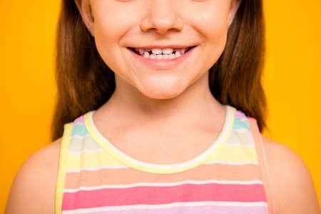 Abgeschnittenes Foto eines charmanten Kindes mit einem zahnigen Lächeln, das ein Tank-Top auf gelbem Hintergrund trägt Standard-Bild