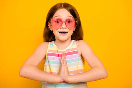 Portrait of cute girl wearing heart-shaped eyeglasses tank-top screaming wow omg isolated over yellow background Stock Photo