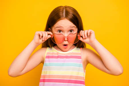 Close up photo of astonished girl touching her specs wearing singlet isolated over yellow background